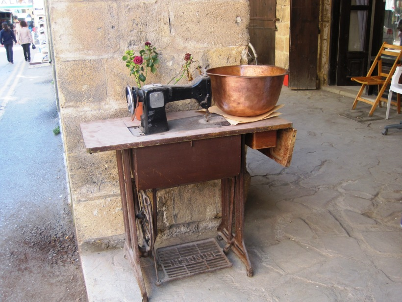 Singer sewing machine, brass bowl and a potted plant.